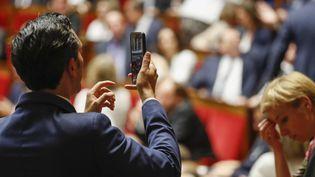 Un député prend l'Assemblée nationale en photo, lors de la séance inaugurale, le 27 juin 2017. (PATRICK KOVARIK / AFP)