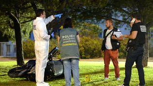 La police scientifique enquête sur le meurtre d'un homme à Marseille, le 18 juillet 2014. (BORIS HORVAT / AFP)