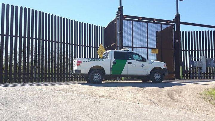 Les véhicules des patrouilleurs de la National Border Control, la police aux frontières, sont visibles des deux côtés de la barrière. (MATHILDE LEMAIRE / RADIO FRANCE)