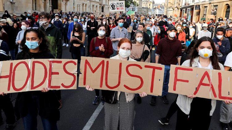"""""""Rhodes doit tomber"""", slogan en référence à la statue ornant le fronton de l'Oriel College d'Oxford. Le 9 juin 2020, des centaines de manifestants ont réclamé, dans les rues d'Oxford, le démontage de la statue. (ADRIAN DENNIS / AFP)"""
