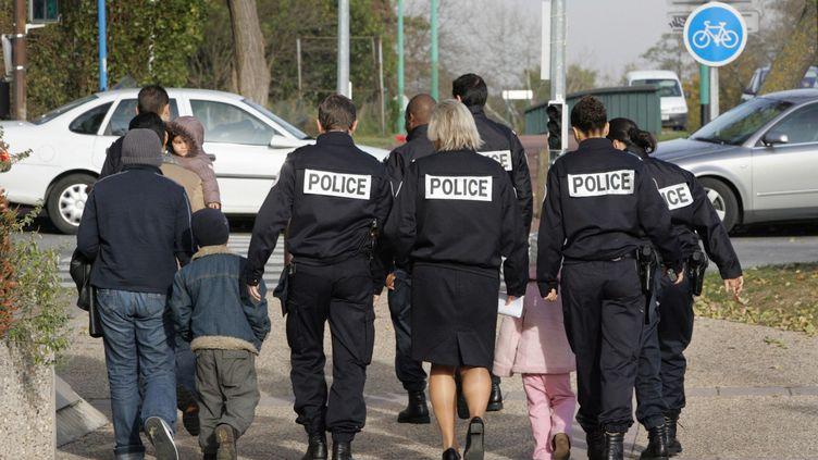 Des membres de la police de l'air et des frontières escortent une famille à la sortie du tribunal de Cergy, vers l'aéroport de Roissy, lors d'une procédure de reconduiteà la frontière, le 10 novembre 2006. (JACK GUEZ / AFP)