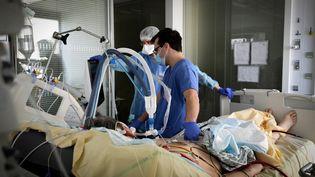 Des médecins au chevet d'un patient hospitalisé en réanimation, le 8 mars 2021 à Boulogne-Billancourt (Hauts-de-Seine). (ALAIN JOCARD / AFP)