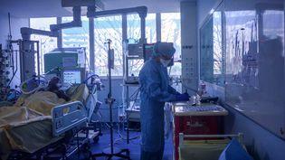 Une infirmière tsoigne une personne malade du Covid-19, dans le service de soins intensifs de l'hôpital Bichat (Paris), le 13 mars 2020. (ANNE CHAON / AFP)