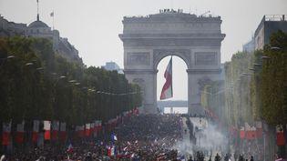 Des supporters sont massés sur les Champs-Elysées, lundi 16 au juillet, pour accueillir les joueurs de l'équipe de France de retour après leur titre mondial. (CHARLY TRIBALLEAU / AFP)