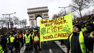 """""""Nous aussi, on veut payer l'ISF"""" proclame cette banderole brandie devant l'Arc de triomphe. (SAMEER AL-DOUMY / AFP)"""