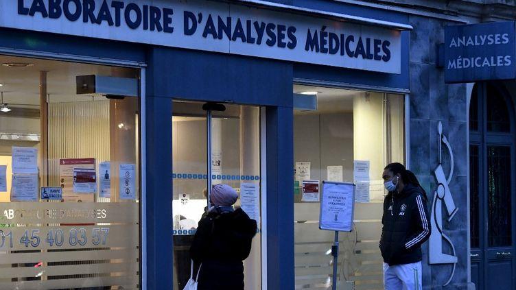 Des patients attendent pour se faire tester au Covid-19 à l'extérieur d'un laboratoire à Paris, le 22 décembre 2020. (STEPHANE DE SAKUTIN / AFP)