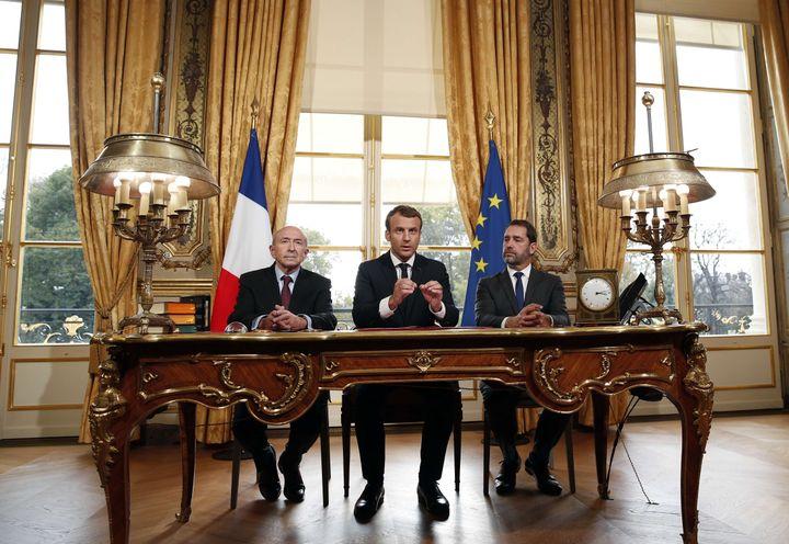 Emmanuel Macron, entouré duministre de l'Intérieur Gérard Collomb (à gauche) et du porte-parole du gouvernement Christophe Castaner, le 30 octobre 2017 au palais de l'Elysée, à Paris. (CHRISTOPHE ENA / SIPA / AP)
