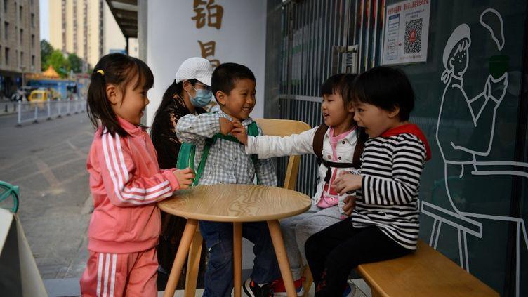 Des enfants jouent à l'extérieur d'un café à Pékin (Chine), le 11 mai 2021. (GREG BAKER / AFP)