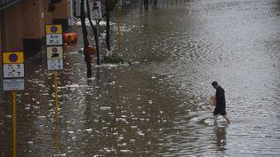 Un homme traverse une rue inondée alors que le typhon Hato frappe Hong Kong, mercredi 23 août 2017. (ANTHONY WALLACE / AFP)