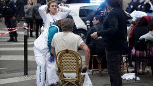 """Un blessé est pris en charge par les équipes de secours. """"On a l'impression d'un état de guerre"""" a raconté un riverain à franceinfo. (GEOFFROY VAN DER HASSELT / AFP)"""