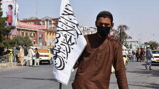Un homme portant le drapeau des talibans dans la ville afghane de Mazâr-e Charîf, le 20 août 2021. (STRINGER / SPUTNIK / AFP)