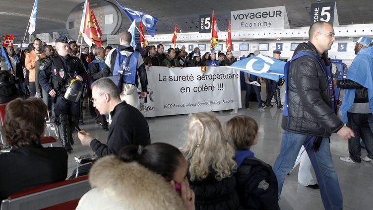Le personnel des sociétés de sûreté de l'aéroport Roissy-Charles de Gaulle (Val-d'Oise)manifeste devant les passagers, le 17 décembre 2011. (PH LAVIEILLE/ LE PARISIEN / MAXPPP)