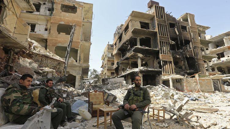 Des soldats du régime syrien au milieu des immeubles détruits de Douma, vendredi 20 avril, en Ghouta orientale (Syrie). (LOUAI BESHARA / AFP)