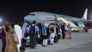 Des personnes ayant fui l'Afghanistan s'apprête àdécolleren direction de Paris depuis l'aéroport d'Abou Dhabi, aux Emirats arabes unis, le 26 août 2021. (ETAT-MAJOR DES ARMEES / AFP)