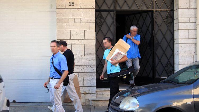 Des policiers quittent le domicile de la famille Benitez à Perpignan (Pyrénées-Orientales), après la disparition de Marie-Josée et Allison, le 1er août 2013. (RAYMOND ROIG / AFP)