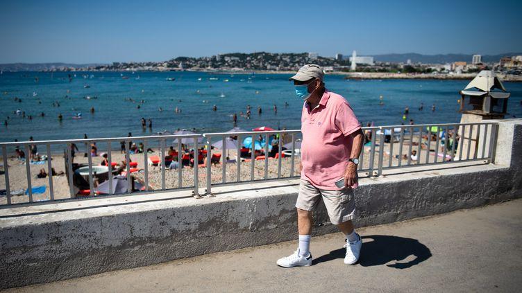 Un passant porte un masque sur le visage, le long de la plage de la Pointe rouge, le 27 juillet 2020 à Marseille (Bouches-du-Rhône). (CLEMENT MAHOUDEAU / AFP)