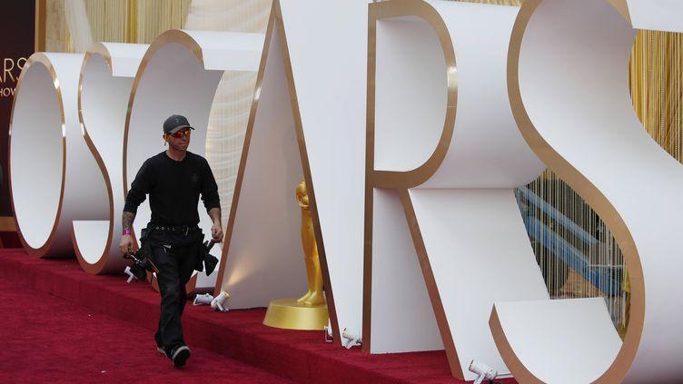 Un technicien marche sur le fameux tapis rouge durant la préparation de la 92e cérémonie des Oscars, samedi 8 février 2020 à Los Angeles. (JOHN LOCHER/AP/SIPA / SIPA)