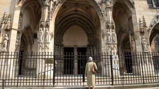Une femme devant l'entrée de l'église Saint-Germain l'Auxerrois à Paris, le 10 avril 2020. (BERTRAND GUAY / AFP)