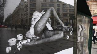 L'une des affiches montre une femme en bas résille, jambes écartées face à l'objectif du photographe. (ERIC FEFERBERG / AFP)
