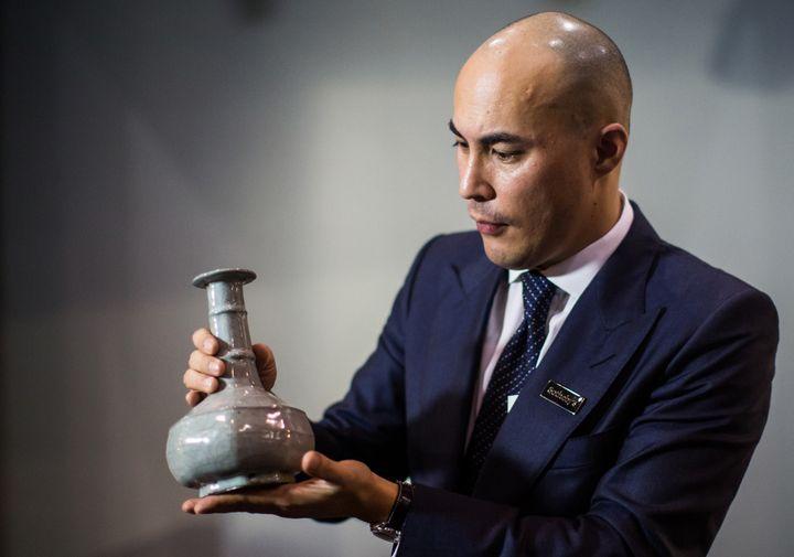 Nicolas Chow de Sothby's montrant le vase octogonal.  (ANTHONY WALLACE / AFP)
