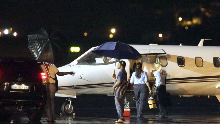Avant l'arrivée de Johnny Hallyday, quelques personnes attendent devant le jet privé qui doit l'emmener vers Los Angeles, dans la nuit du 30 au 31 août 2012, en Martinique. (KENZO TRIBOUILLARD / AFP)