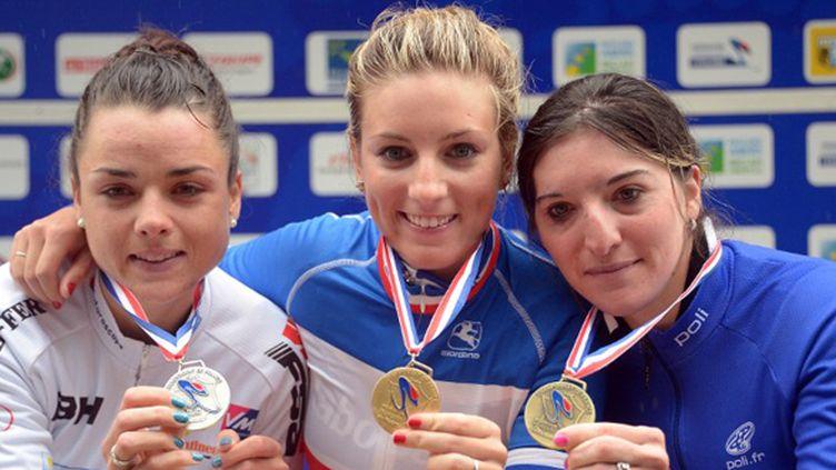 Pauline Ferrand Prevot (C) montre sa médaille sur le podium entourée de la seconde Audrey Cordon (G) et la troisième Medlodie Lesueur (D) (DAMIEN MEYER / AFP)