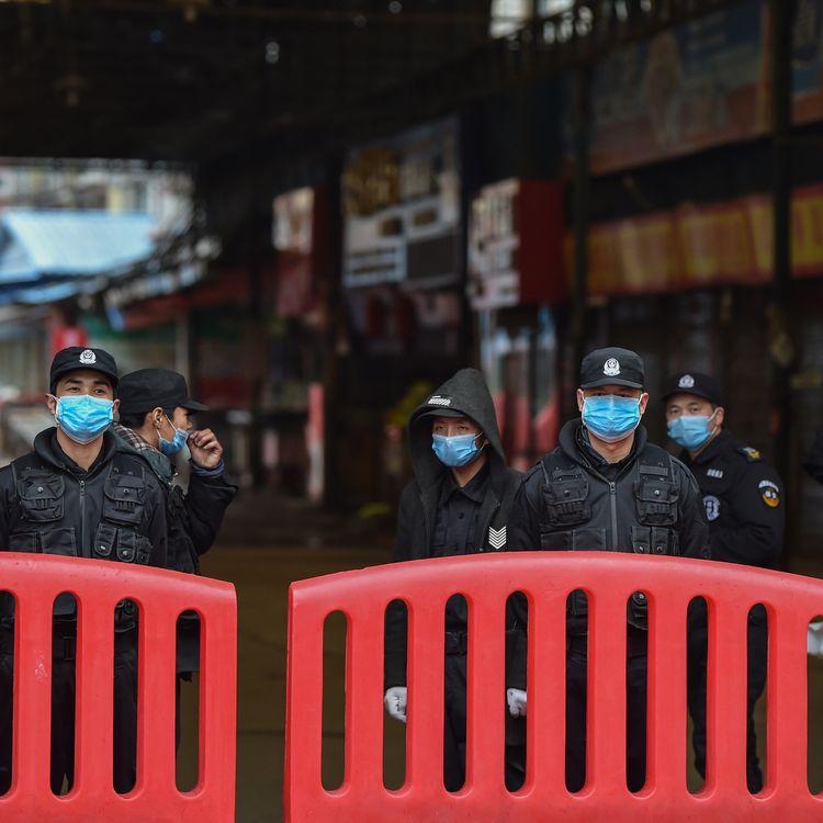 Des policiers gardent l'entrée du marché de gros de fruits de mer de Huanan, à Wuhan, soupçonné d'être le foyer de l'épidémie de coronavirus, le 24 janvier 2020, depuis fermé par les autorités chinoises. (HECTOR RETAMAL / AFP)