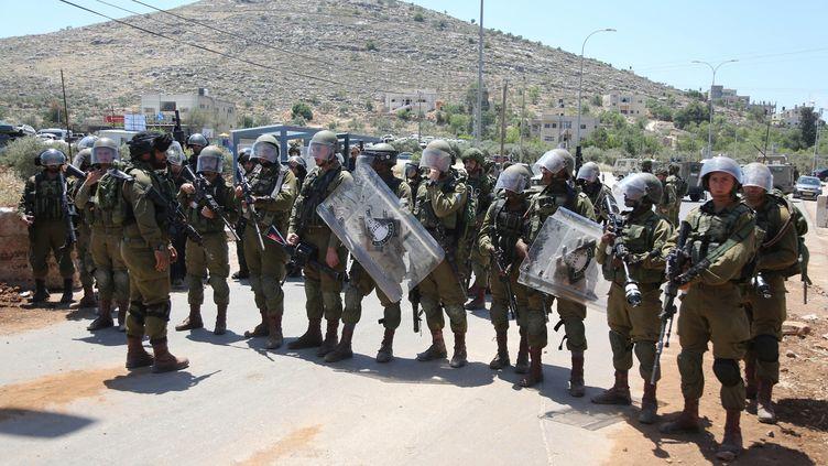 Des soldats israéliens mobilisés face à des manifestants palestiniens dénonçant le mur de séparation et la colonisation, le 12 mai 2017 à Nebi Saleh, un village près de Ramallah (Cisjordanie). (ISSAM RIMAWI / ANADOLU AGENCY / AFP)
