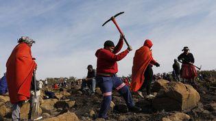 Une femme creuseà la recherche de ce qu'elle pense être des diamants après la découverte de pierres non identifiées dans le village de KwaHlathi près de Ladysmith, en Afrique du Sud, le 15 juin 2021. (PHILL MAGAKOE / AFP)