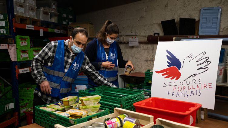 Les bénévoles trient les produits par date de péremption, à Paris, le 1er avril 2020. (ANTOINE MARTIN / HANS LUCAS)