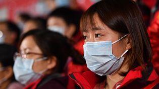 Deux membres du personnel médical de l'hôpital deNanfang, en Chine, participent à une cérémonie àHubei, le 10 février 2020. (LIU DAWEI / XINHUA / AFP)
