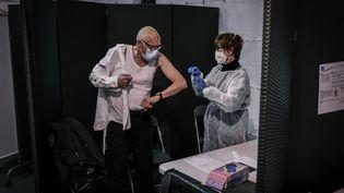 Un patient reçoit une dose de vaccin contre le Covid-19 au Palais des sports de Lyon, le jeudi 14 janvier 2021. (JEAN-PHILIPPE KSIAZEK / AFP)