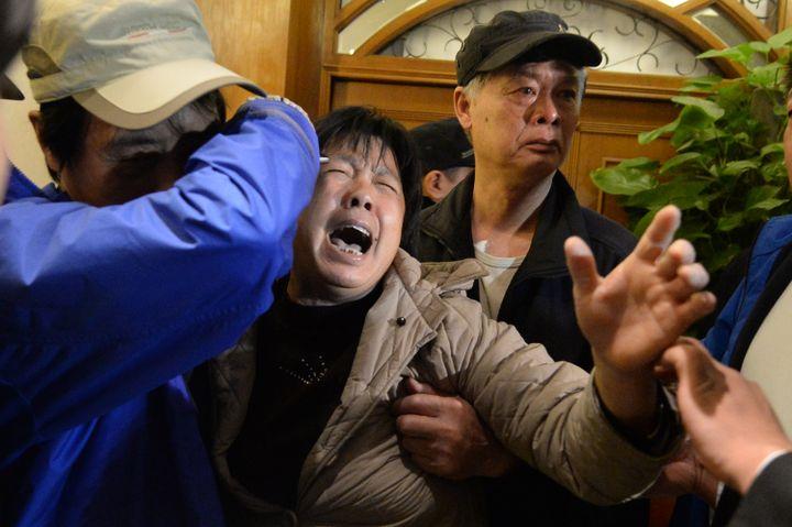 Cris et sanglots dans un hôtel de Pékin (Chine) où les familles ont appris la mort de leurs proches. (GOH CHAI HIN / AFP)