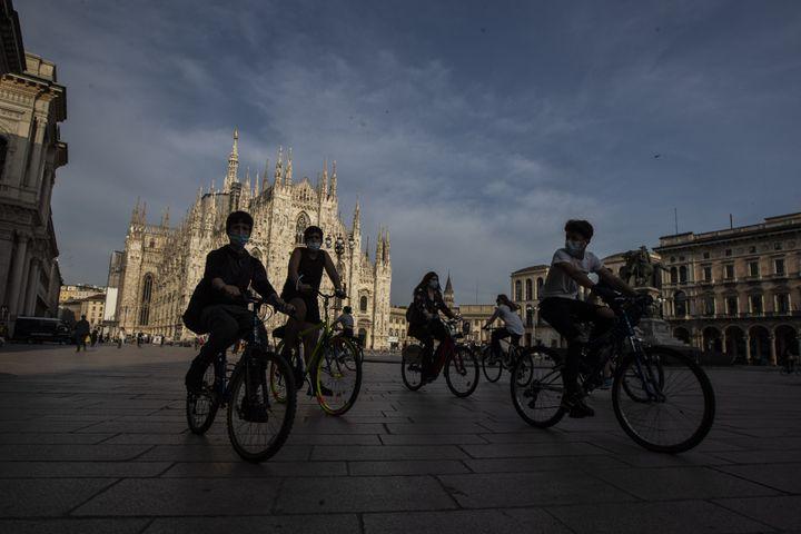 Des cyclistes devant la cathédrale Duomo à Milan (Italie) le 18 mai 2020. (LUCA BRUNO / AP)