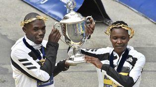 Benson Kipruto etDiana Kipyogei soulèvent leur trophée au 125e marathon de Boston, le 11 octobre 2021. (JOSEPH PREZIOSO / AFP)