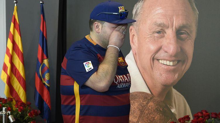 Un supporter du Barça, en larmes devant la photo de Cruyff.  (LLUIS GENE / AFP)