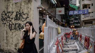 Une passante se bouche les oreilles pour se protéger du bruit de travaux à Hong Kong, le 9 juillet 2013. (PHILIPPE LOPEZ / AFP)