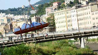Les secours transportent un corps après l'effondrement du pont Morandi à Gênes, le 14 août 2018. (MASSIMO PINCA / REUTERS)