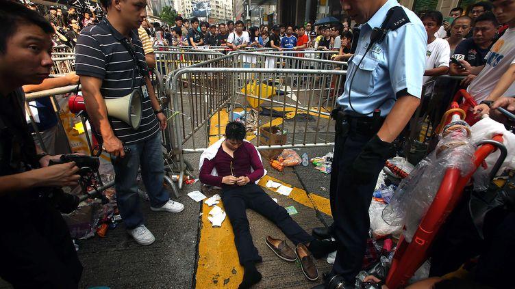 Un militant pro-démocratie blessé après les heurts en marge des manifestations à Hong Kong, le 3 octobre 2014. (STEPHEN SHAVER / NEWSCOM / SIPA )