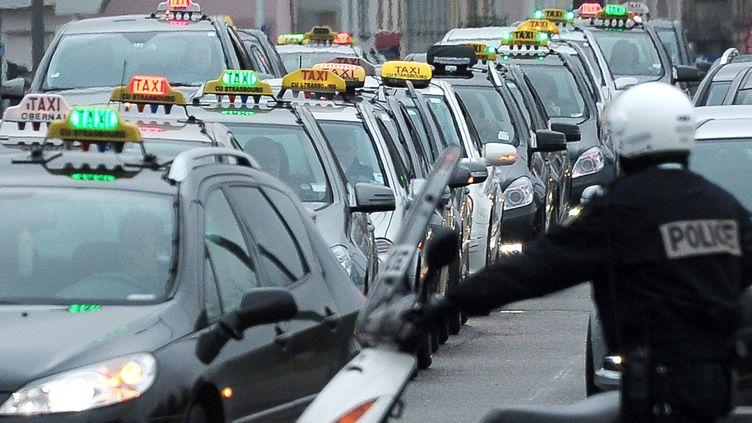 Un policier encadre une mobilisation des chauffeurs de taxis, à Strasbourg (Haut-Rhin),le 10 janvier 2013. (FREDERICK FLORIN / AFP)
