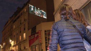 Spectateurs dans la rue Daubanton qui regarde un film sur la façade du cinéma La Clef (France 3 Paris Ile de France)