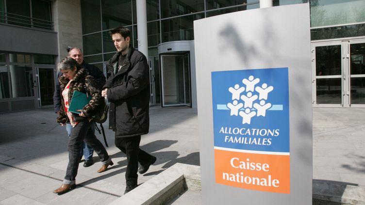 Des personnes quittent le siège parisien de la Caisse nationale des allocations familiales (Cnaf), le 27 mars 2007. (JACK GUEZ / AFP)