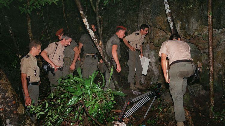 Des militaires français des forces armées de la Nouvelle-Calédonie inspectent, le 6 mai 1988 à Ouvéa, l'entrée de la grotte de Gossanah, dans laquelle des militants indépendantistes calédoniens avaient pris des gendarmes en otages. (- / AFP)