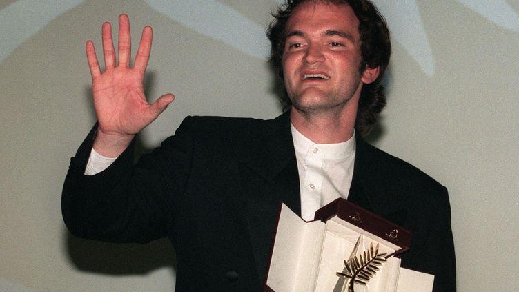 """Quentin Tarantino reçoit la Palme d'or pour """"Pulp Fiction"""" à Cannes le 23 mai 1994 (PATRICK HERTZOG / AFP)"""