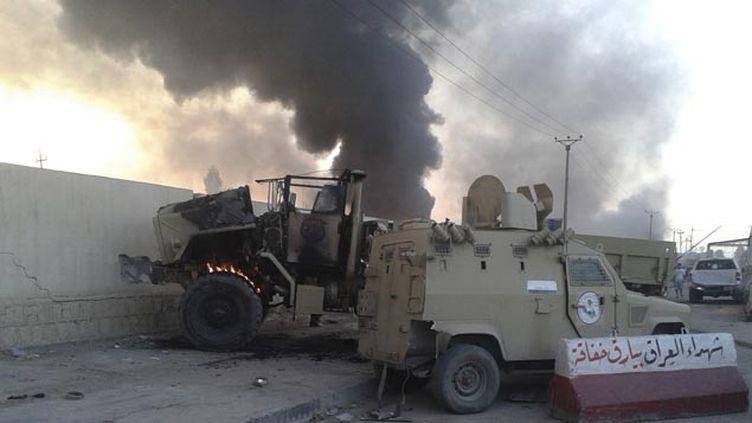 (Des voitures des forces de l'ordre irakiennes incendiées à Mossoul © Reuters)