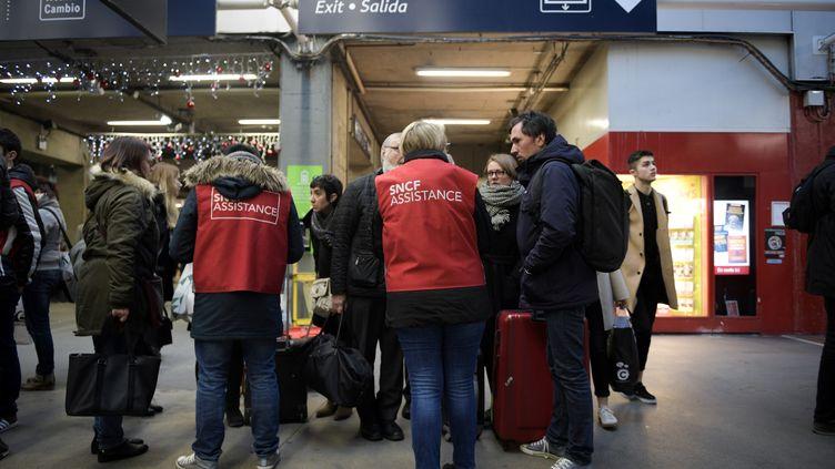 Des naufragés du rail pris en charge par du personnel SNCF, le 3 décembre 2017 à la gare Montparnasse, à Paris. (MARTIN BUREAU / AFP)