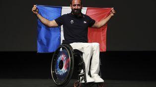 Le porte-drapeau de la France aux Jeux paralympiques, Michaël Jeremiasz, pose à Paris, le 19 juillet 2016. (JACQUES DEMARTHON / AFP)