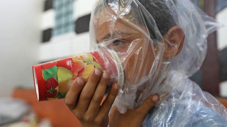 Un enfant syrien teste un masque à gaz de fortune, à MaarChourin, dans la province d'Idleb (Syrie) le 11 septembre 2018. (OMAR HAJ KADOUR / AFP)
