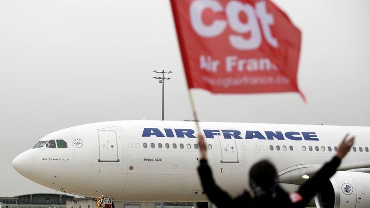 Une employée d'Air France agite un drapeau de la CGT devant un avion de la compagnie à l'aéroport de Roissy, le 1er octobre 2015. (KENZO TRIBOUILLARD / AFP)