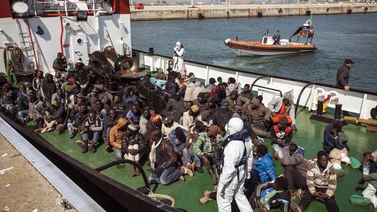 (Des migrants récupérés par un cargo accostent dans un port italien à Corigliano. © Maxppp)